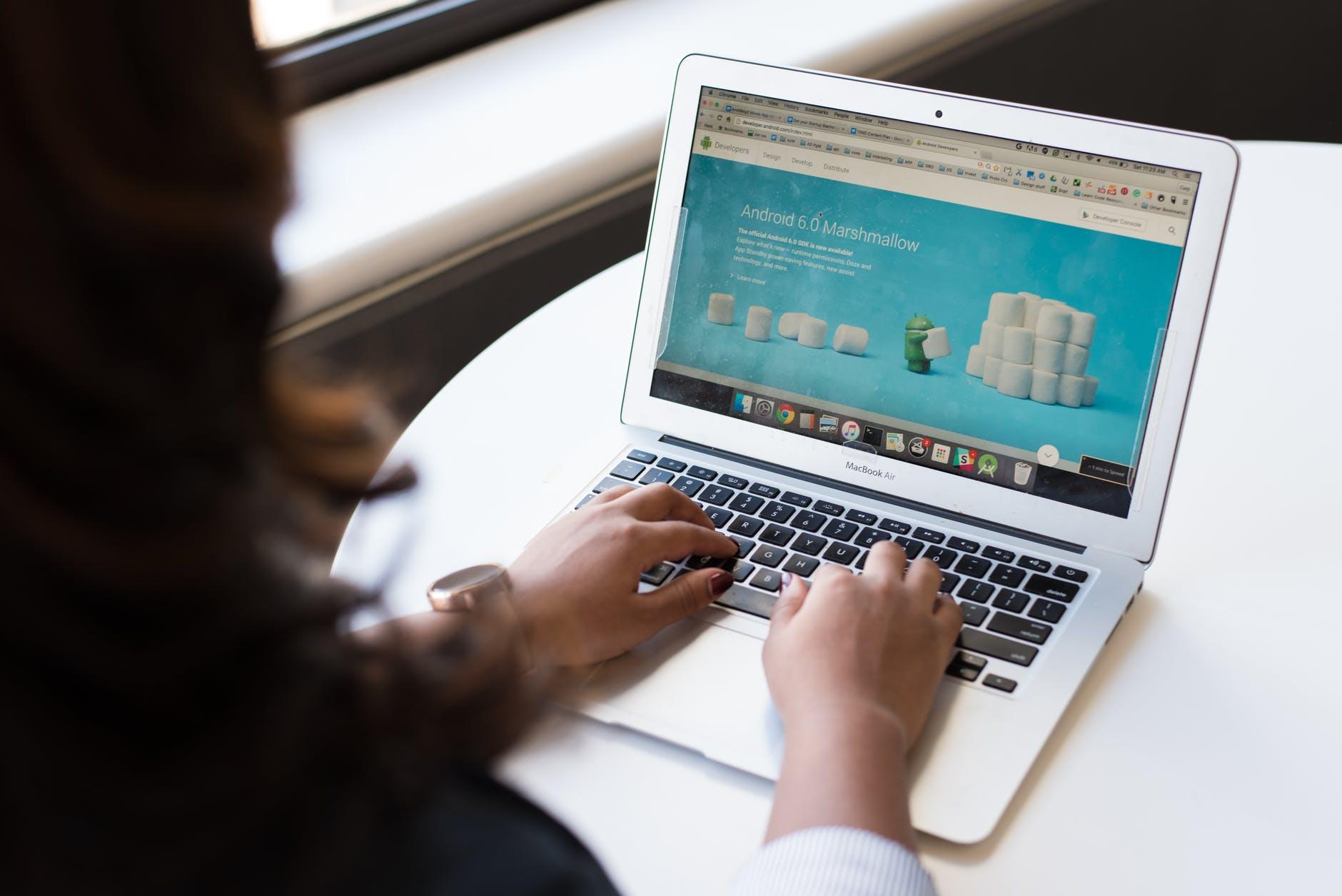 woman sitting near table using macbook